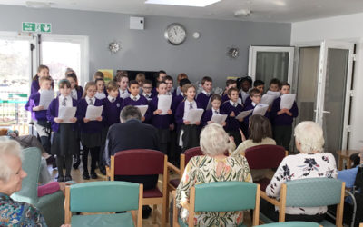 A group of primary school children singing Christmas songs for the residents of The Old Downs Residential Care Home