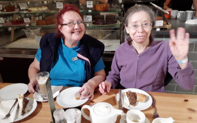 An Abbotsleigh Care Home resident and carer sat in a cafe with coffee and cake