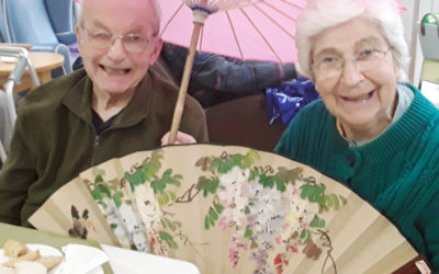Lady and gentlemen resident of Abbotsleigh Care Home, holding a Chinese umbrella and fan