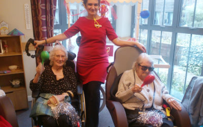 Two seated residents with a staff member between them enjoying musical instruments at Hengist Field Care Home