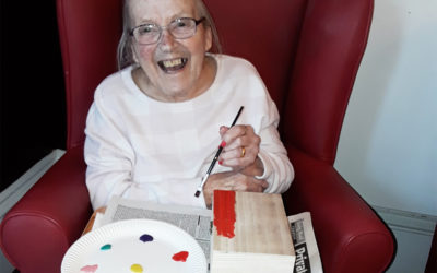 Resident painting a wooden treasure box with colourful paints at Lulworth House Residential Care Home