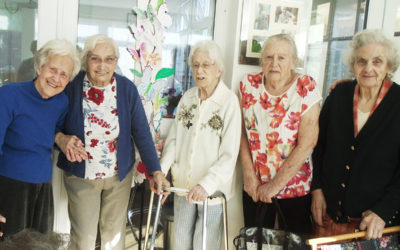 A group of lady residents standing together smiling at the camera at The Old Downs Residential Care Home