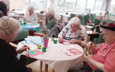 Residents doing St Patrick Day arts and crafts seated around tables together
