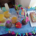 A table of fruit cocktails with a Hawaiian theme