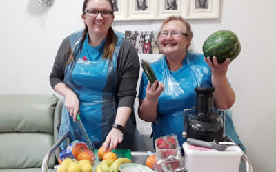 Two staff member standing at a trolley with fruit ready to go into a blender