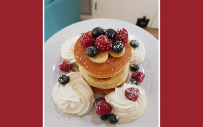 A stack of pancakes, decorated with cream and fruit
