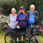 Lady resident at The Old Downs Residential Care Home, standing next to her husband and daughter, who is dressed in cycling gear and holding a bicycle