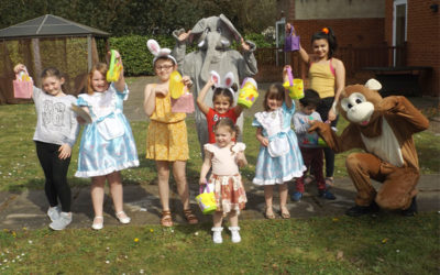 A group of children enjoying an Easter egg hunt in the garden at Princess Christian Care Home