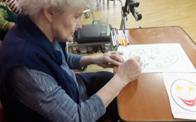 Female resident sitting colouring in a picture of an Easter egg