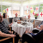 Residents around a table enjoying a St George's Day afternoon tea