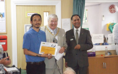 Staff member receiving a recognition certificate from Princess Christian Home Manager and the Mayor of Surrey Heath