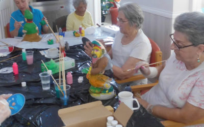 Residents painting gnomes together around a table