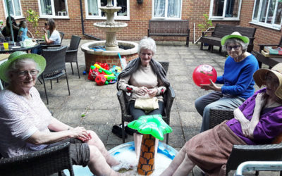 Lady residents sitting in the garden with their feet in a paddling pool