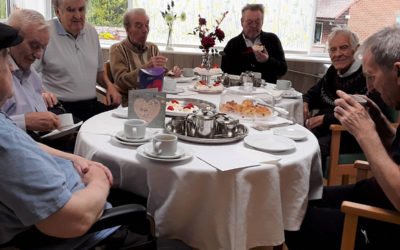 Male residents sitting around a table celebrating Fathers Day with a coffee morning at The Old Downs Residential Care Home