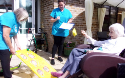 Resident throwing a bean bag into a target outside in the garden at Loose Valley Care Home