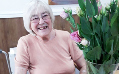Lady resident at Sonya Lodge Residential Care Home smiling to camera with her flower arrangement