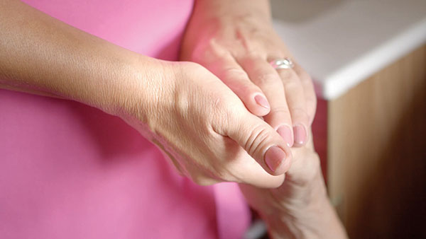 Carer holding elderly care home residents hand